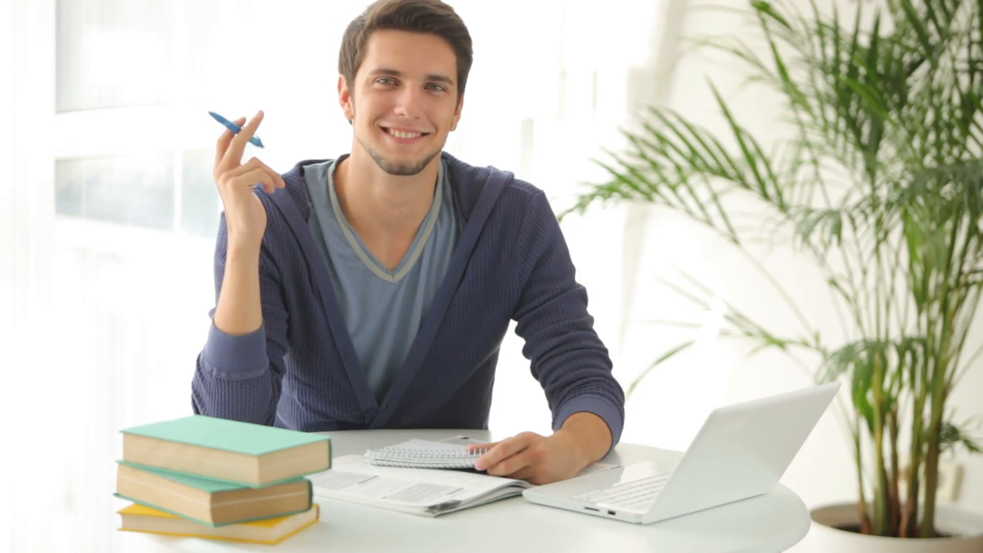 young-man-sitting-at-table-studying-with-books-and-laptop_vjnzszvrg__F0000